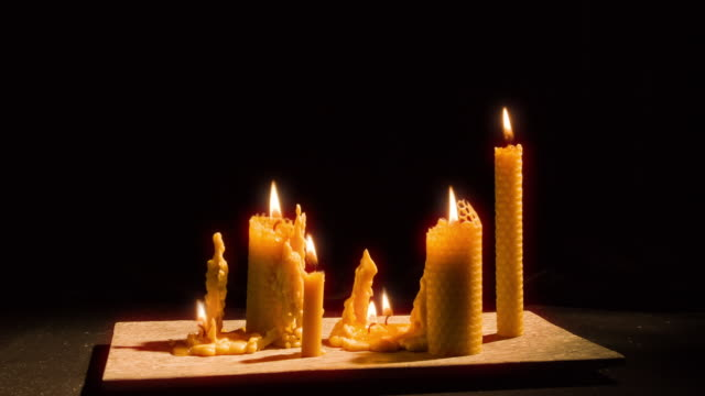 Time-Lapse wax candles burning down to leave wax on a tray. Slight camera move