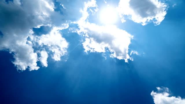 4k zeitraffer - weiße wolken am blauen himmel mit sonnenstrahlen fliegen - aufnahme von unten stock-videos und b-roll-filmmaterial
