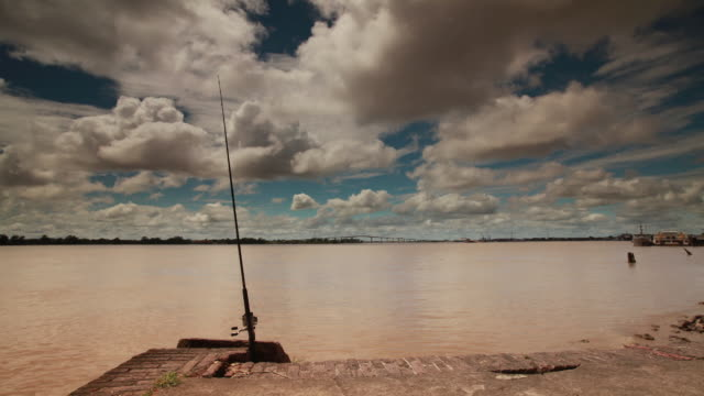timelapse wide shot of fishing pole on edge of stone jetty overlooking river - fishing rod stock videos & royalty-free footage