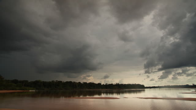 Timelapse wide shot of grey clouds rolling across sky over sandy river inlet