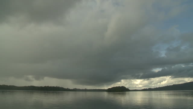 Timelapse wide shot of storm clouds rolling in across river