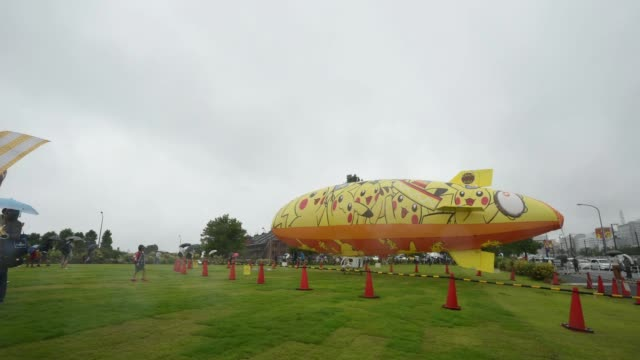 Timelapse wide shot people take photographs in front of an airship adorned with the Pikachu character from Nintendo Co's Pokemon franchise during a...