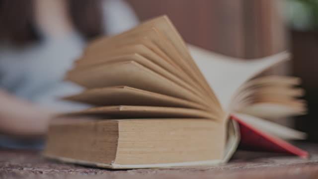 vidéos et rushes de femme de timelapse affichant un livre dans le café - objet en papier