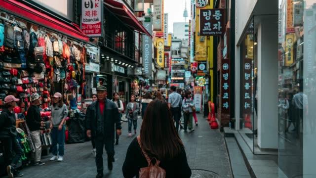 timelapse young asiatin reisende reisen und einkaufen in myeongdong straßenmarkt in seoul, südkorea. myeong-dong bezirk ist die beliebteste shopping-markt in seoul city. - korea stock-videos und b-roll-filmmaterial