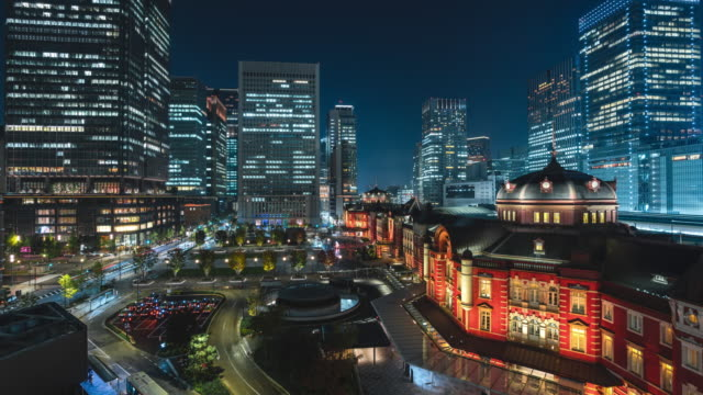 4k time-lapse: zoom in night scene of pedestrian tourist crowd walking and car traffic at tokyo station downtown near train station, rush hours - stepping stock videos & royalty-free footage