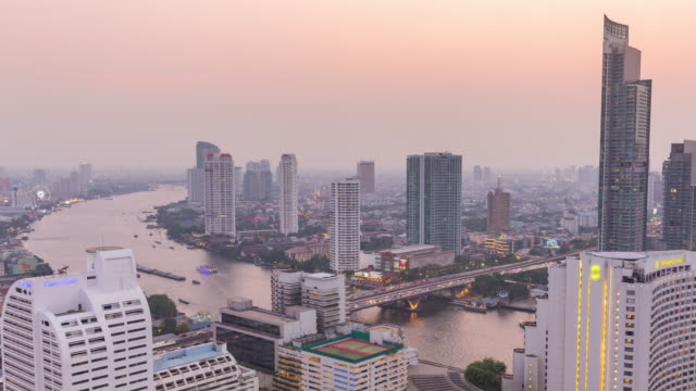 4k time-lapse : zoom out effect modern business building and chao phraya river from day to dusk in bangkok. - day to dusk stock videos & royalty-free footage