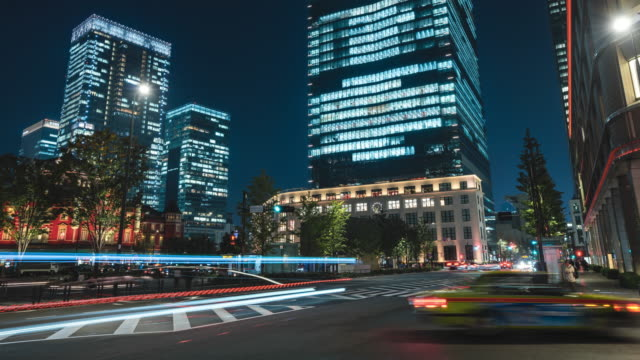 4k time-lapse: zoom out in night scene of pedestrian tourist crowd walking and car traffic at tokyo station downtown near train station, rush hours - stepping stock videos & royalty-free footage