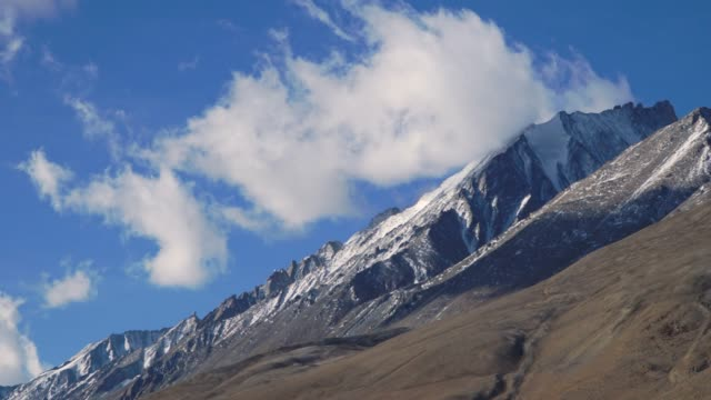 4k ,time-lapse, zoom out; snow mountain and green field in leh, india. - hill stock videos & royalty-free footage