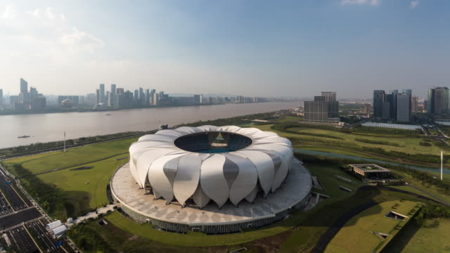 4k time-lapse:hangzhou olympic sports center against the qiantang river,hangzhou,china - hangzhou stock videos & royalty-free footage