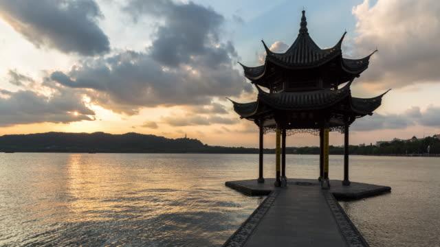 vídeos de stock e filmes b-roll de 4k time-lapse:silhouetted pavilion against sunbeams from setting sun,hangzhou,china - belveder