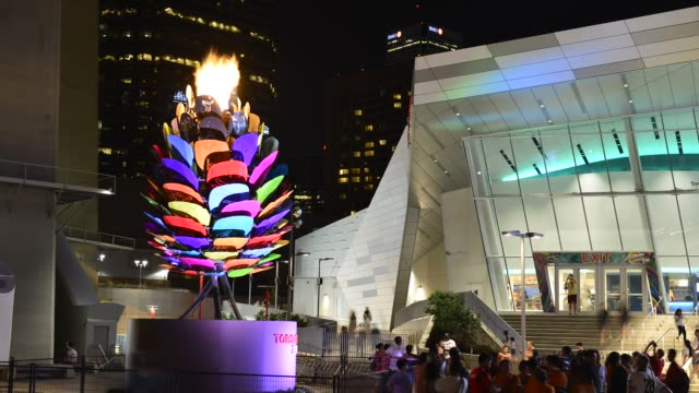 the pan am flame burns brightly in the cn tower plaza or square while people or tourist visit the new attraction in the multicultural city - パンアメリカンハイウェイ点の映像素材/bロール
