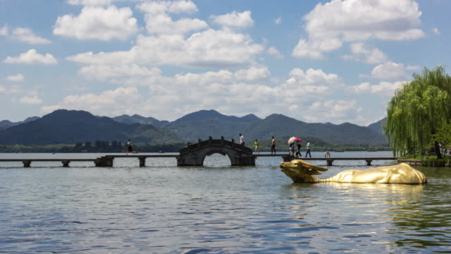 4k time-lapse:tourists walking along stone bridge on the west lake,hangzhou,china - rappresentazione di animale video stock e b–roll