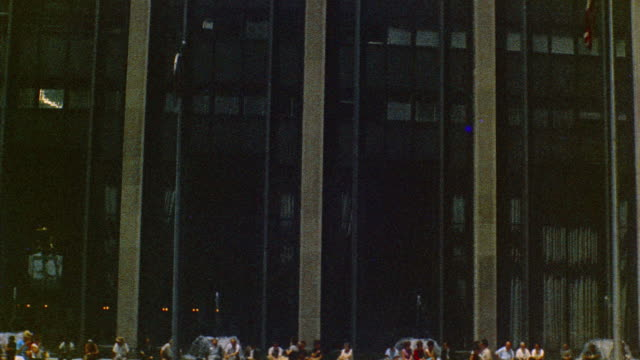 1969 MS TU TD Time-Life Building from across 6th avenue with office workers sitting in front / New York City