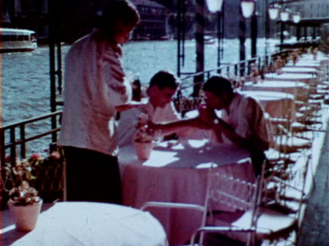time-life correspondent robert copland sitting w/ british director david lean at outdoor waterfront cafe table, waiter fg. - beverly hills stock videos & royalty-free footage