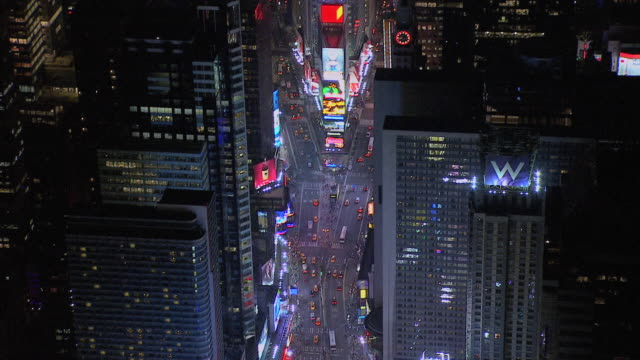 aerial times square amongst the buildings of new york city, lit up at night, and traffic driving on streets / new york, united states - heranzoomen stock-videos und b-roll-filmmaterial