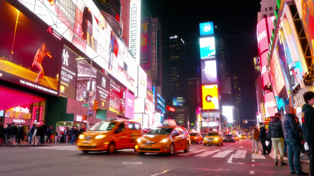 times square illuminated with many colors at night. yellow taxis. tourism. travel destination. - yellow taxi video stock e b–roll