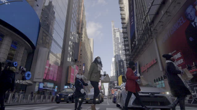 times square new york 2021  masked tourists super slo-mo cross road in front of screens billboards - straßenmarkierung stock-videos und b-roll-filmmaterial