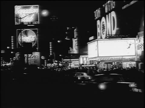 B/W 1967 Times Square with neon signs + traffic at night / NYC / newsreel