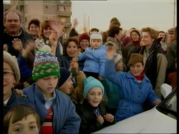 "vidéos et rushes de timisoara: gateway marking entrance to city track forward apartment buildings track l-r seq cheering children on pavement sof - one says ""ceausescu... - communisme"