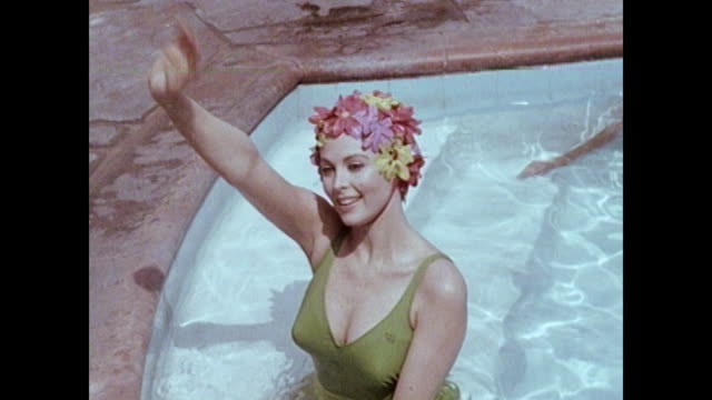 Tina Louise at swimming pool and the twist Tina puts on a flowered bathing cap and swims a few laps waves to someone / She does the twist Tina at a...