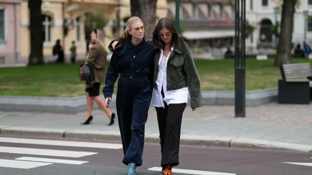 Tine Andrea wearing a corduroy button shirt and croppe pants and Darja Barannik wearing black pants green jacket and a white button shirt are seen...