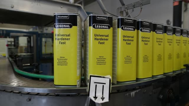 Tins of Sikkens Autocoat pass along the packing line inside the Akzo Nobel NV paint and coatings factory in Sassenheim Netherlands on Thursday Aug 24...
