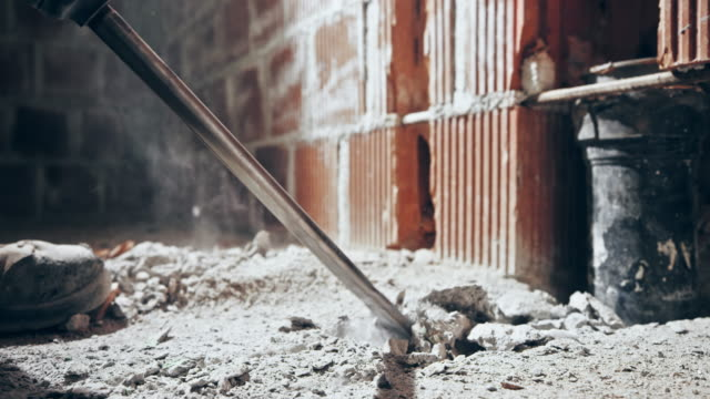 ld tiny concrete fragments flying around as the chisel of the jackhammer pushes through the concrete floor - calcestruzzo video stock e b–roll