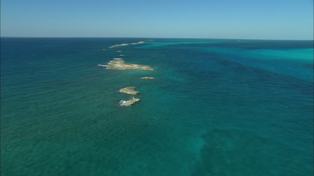AERIAL Tiny rocky islands in shallow Caribbean waters near Eleuthera Island, Bahamas
