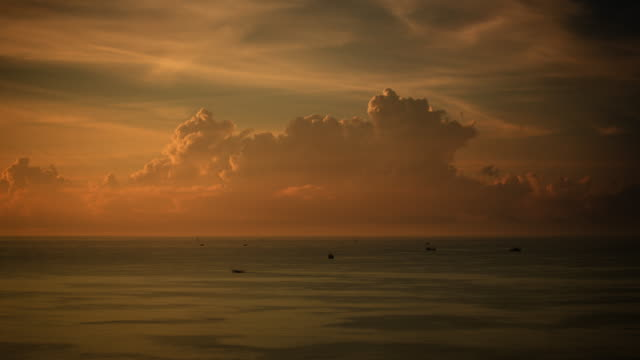 Tiny seagoing boats with huge cloud formations on the horizon