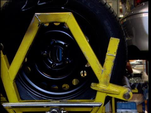 stockvideo's en b-roll-footage met tire fixed onto car in automobile factory - aan elkaar bevestigd