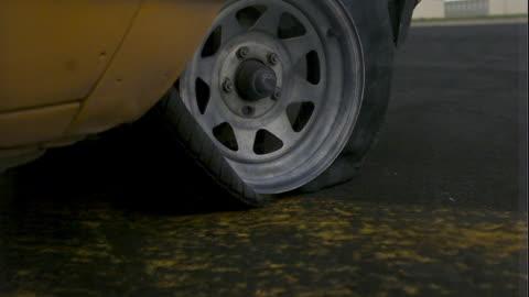 vídeos y material grabado en eventos de stock de a tire gets punished by the rim as it rotates without air. - plano descripción física