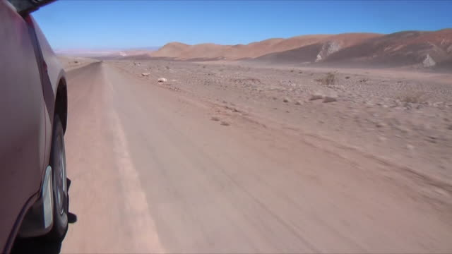 side pov tire of car driving through desert landscape, san pedro de atacama, el loa, chile - san pedro de atacama stock videos & royalty-free footage