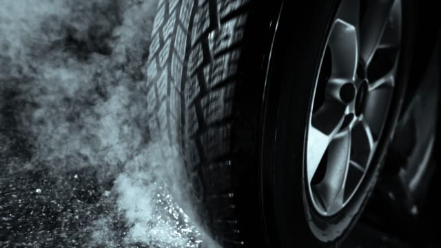 slo mo tire rotating on the ground and causing smoke - tyre stock videos & royalty-free footage