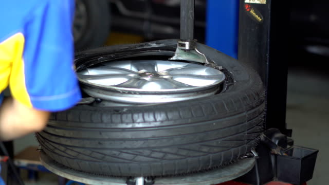Tire service Man put on tyre on car wheel by special tool