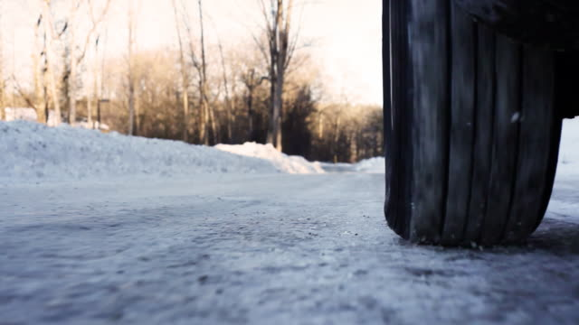 stockvideo's en b-roll-footage met tire slipping on ice extreme low angle - autoband