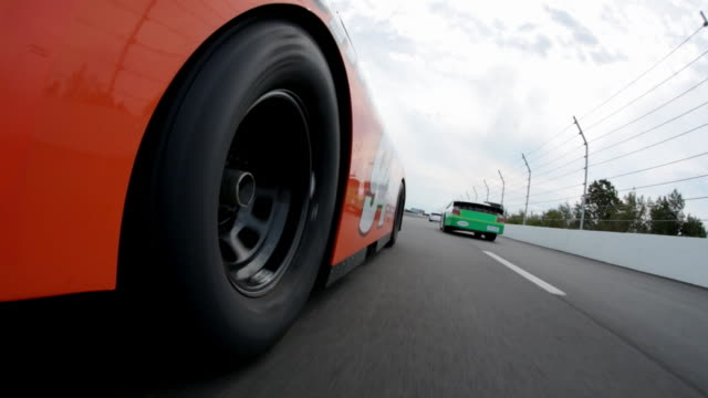 tire spins as orange stock car follows behind green car on race track straightaway. - moving past stock videos & royalty-free footage
