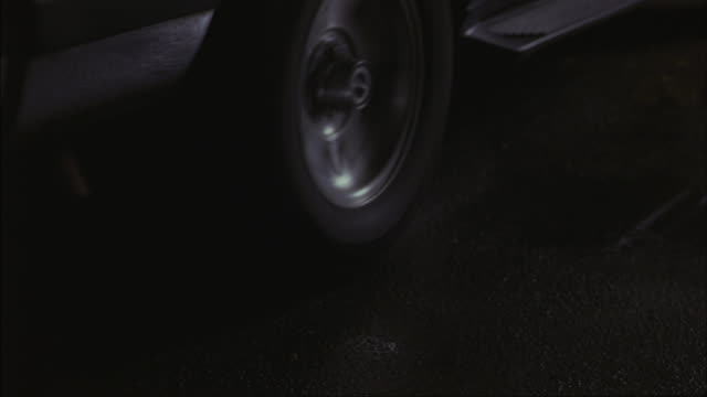 A tire spins in place as a car peels out.