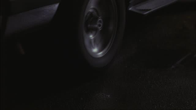 vidéos et rushes de a tire spins in place as a car peels out. - tournoyer