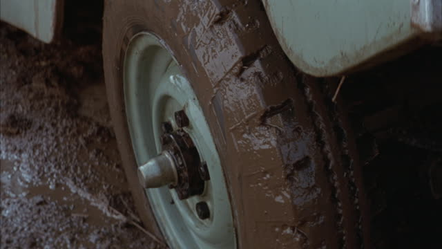 A tire spins uselessly in the mud and sprays muddy water.