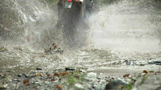 SLO MO MS Tire tearing through puddle as man rides dirt bike away on dirt road through forest / Stowe, Vermont, USA
