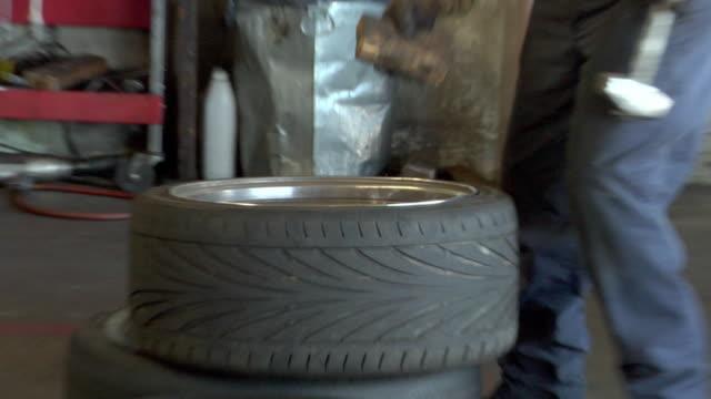 ms zo tire technician bangs rim back into place / los angeles, california, usa - 中年の男性だけ点の映像素材/bロール