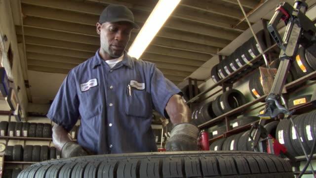 MS TD PAN Tire technician fills air into tire / Los Angeles, California, USA
