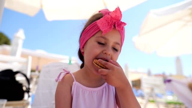 müde entzückende mädchen essen einen keks für einen snack am strand nach der spielzeit - haarschmuck stock-videos und b-roll-filmmaterial