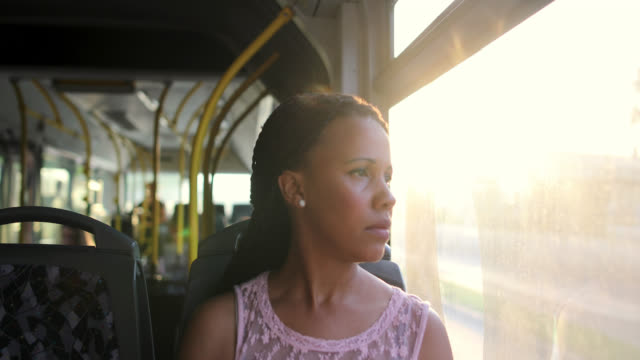 tired and concerned woman thinking about her problems while sitting in a bus and looking through the window - autobus video stock e b–roll