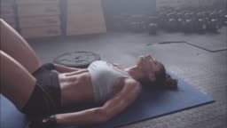 Tired and exhausted female athlete lying on gym floor