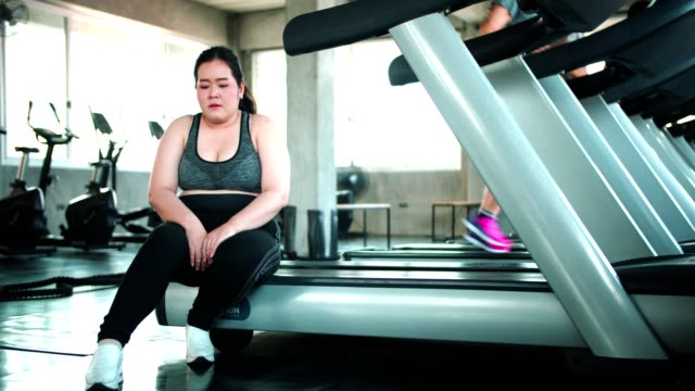 tired and exhausted overweight female sitting on treadmill - treadmill stock videos & royalty-free footage