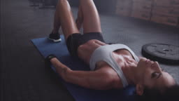 Tired and exhausted sportswoman resting on gym floor