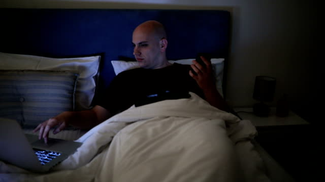 müde glatzkopf arbeiten im bett - erschöpfung stock-videos und b-roll-filmmaterial