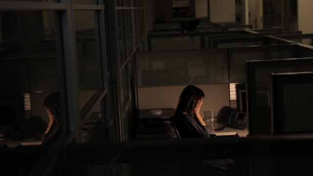 tired business woman working late rubbing her eyes in an empty office