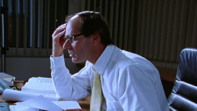 PROFILE tired businessman at desk covered with papers rubbing forehead + taking off glasses/ zoom in dolly shot out